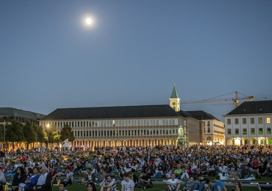 The image shows the forecourt of Karlsruhe Palace, filled with the audience of the Schlosslichtspiele