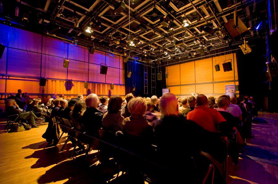 Der ZKM_Kubus mit vollbesetzer Reihenbestuhlung mit Blick auf Bühne