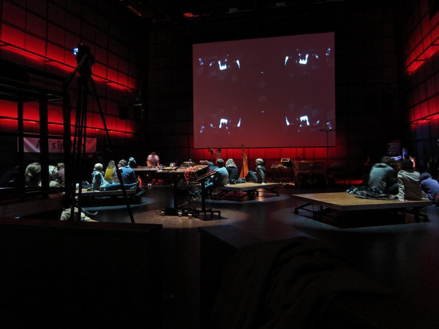 Unbestuhltes ZKM_Medientheater mit Menschen, die auf dem Boden sitzen