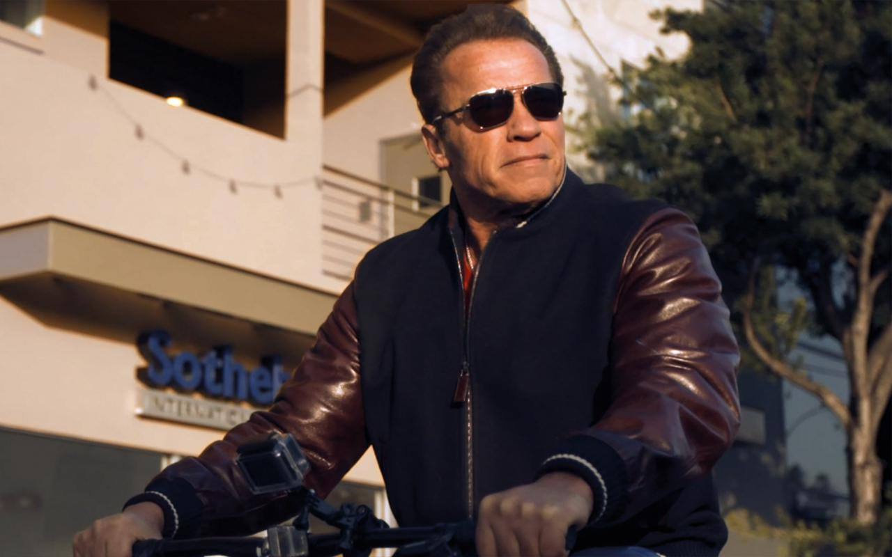 Arnold Schwarzenegger rides a bicycle with sunglasses.