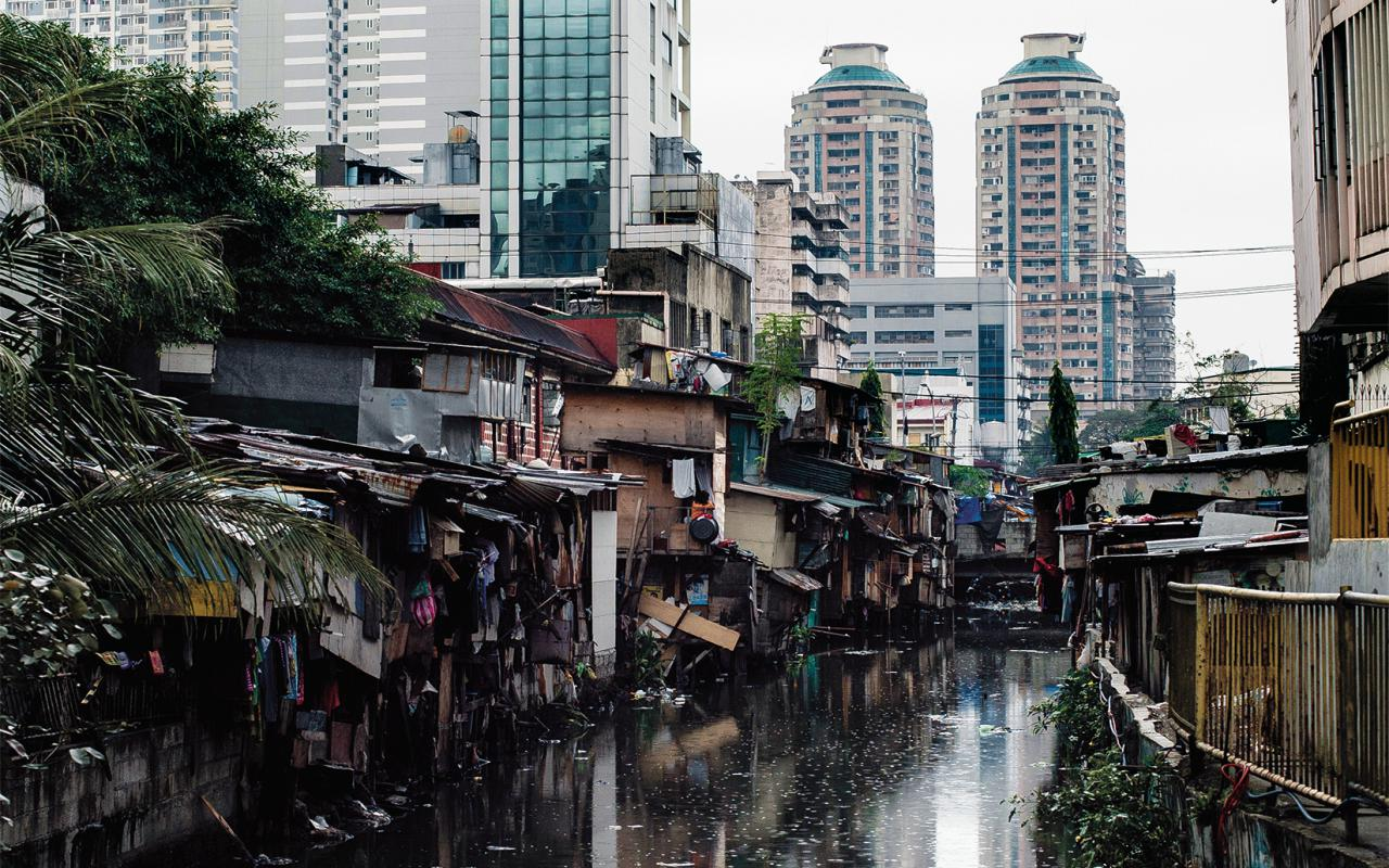 The picture shows dilapidated huts on a dirty river in front of modern high-rise facades.