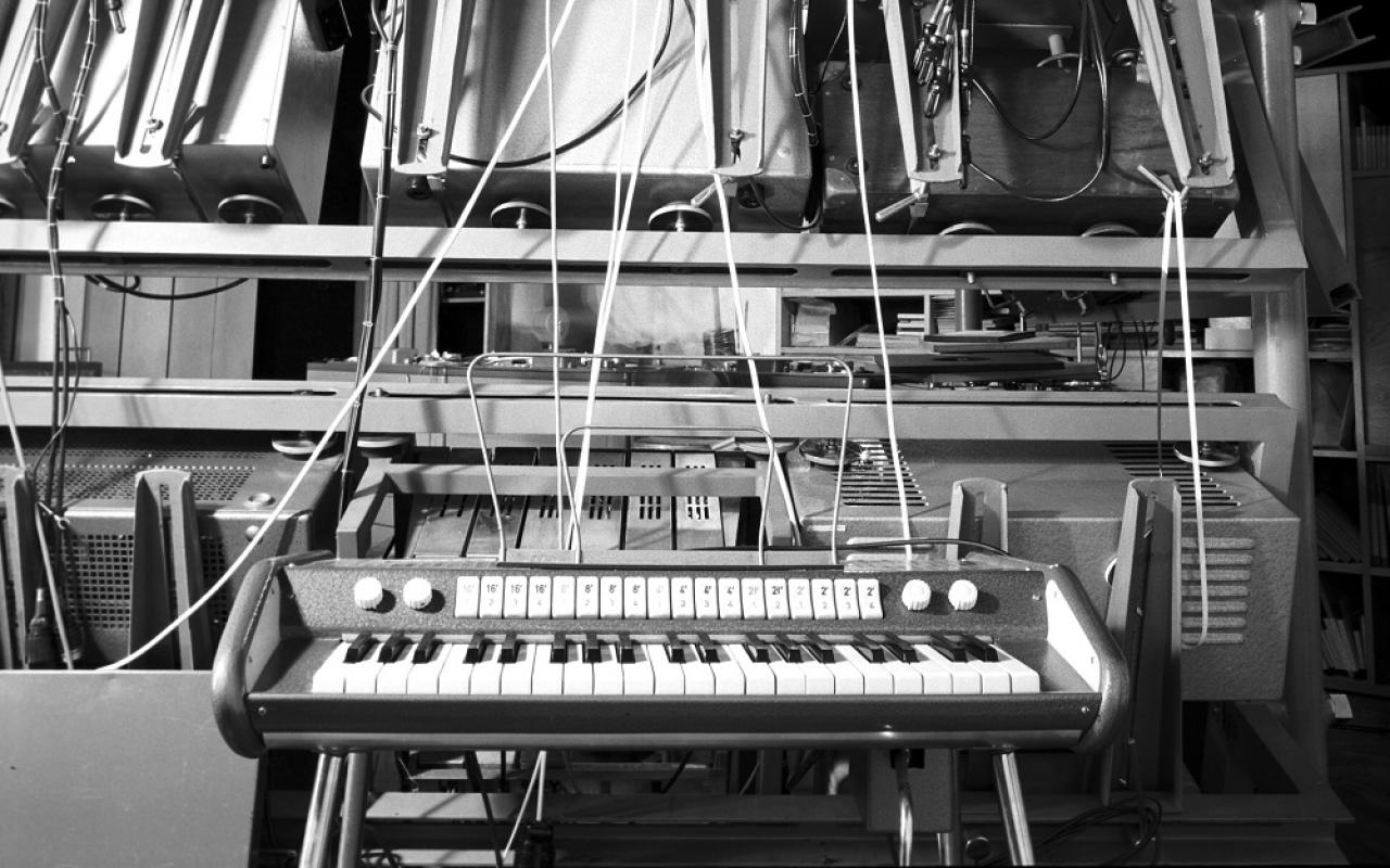 A black and white picture shows an electric piano in front of cables and computers.