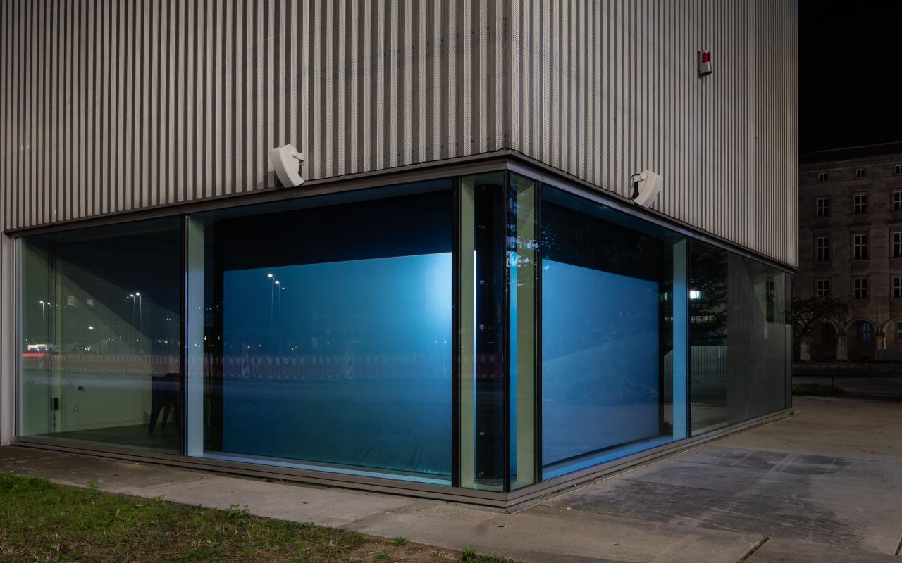Zu sehen ist eine gläserne Fassade, deren Ecke blau beleuchtet wird