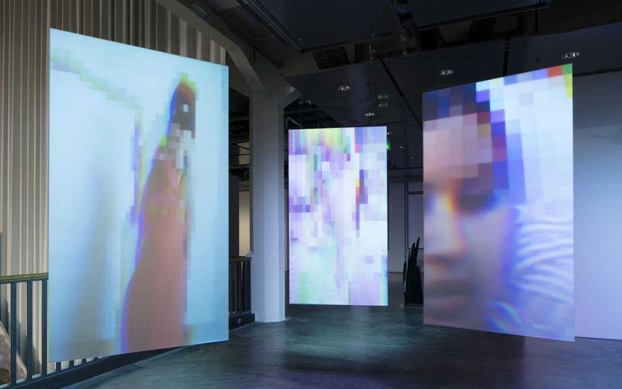 Drei leuchtende Tafeln, auf denen verpixelte Bilder zu sehen sind.