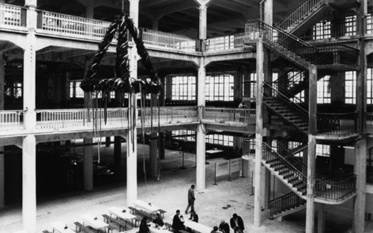 S / W photograph of the celebrations for topping the hall. Visitors sit on beer benches. Above them, the topping-out wreath.