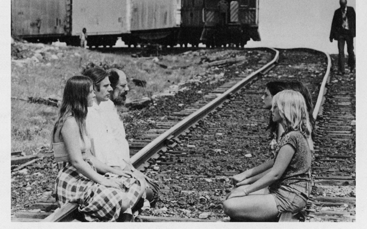 Auf einem Bahngleis sitzen sich Menschen gegenüber. Von hinten naht ein Zug.