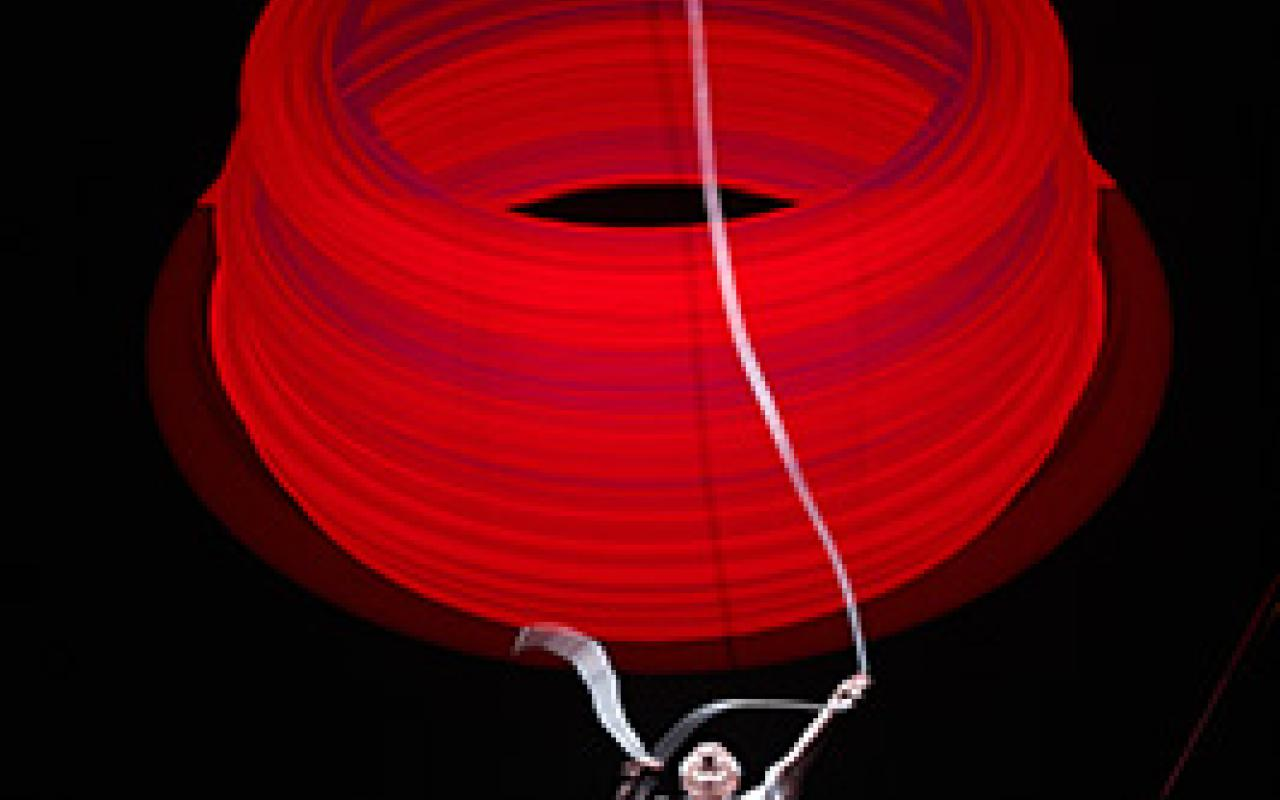 A man handle a huge red ring in front of a black background