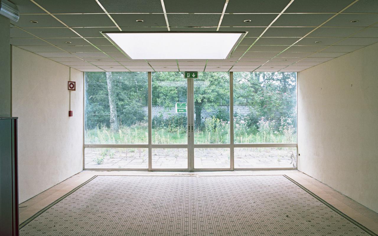 Ein leerer Raum mit großen Fensterfront mit Blick in einen begrünten Außenbereich.
