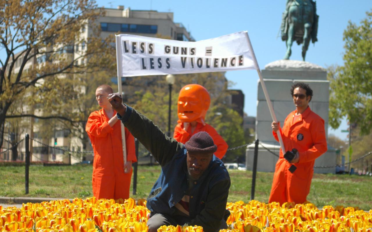 Ein Mann im Blumenbeet hebt seine rechte Faust als Zeichen des Protests. Hinter ihm drei Männer mit einem Transparent.