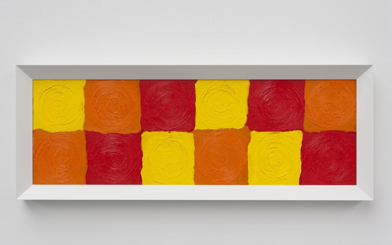 Zwölf farbig gemalte Quadrate in zwei Reihen übereinander in den Farben Gelb, Orange und Rot. Als Bild hängt es an der Wand und ist weiß gerahmt.
