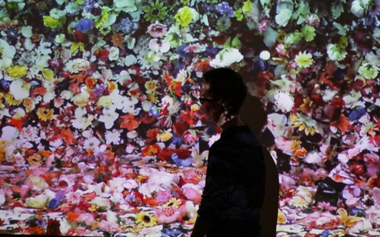 Eine Frau steht vor einer Leinwand, auf der unzählig viele bunte Blumen zu sehen sind.