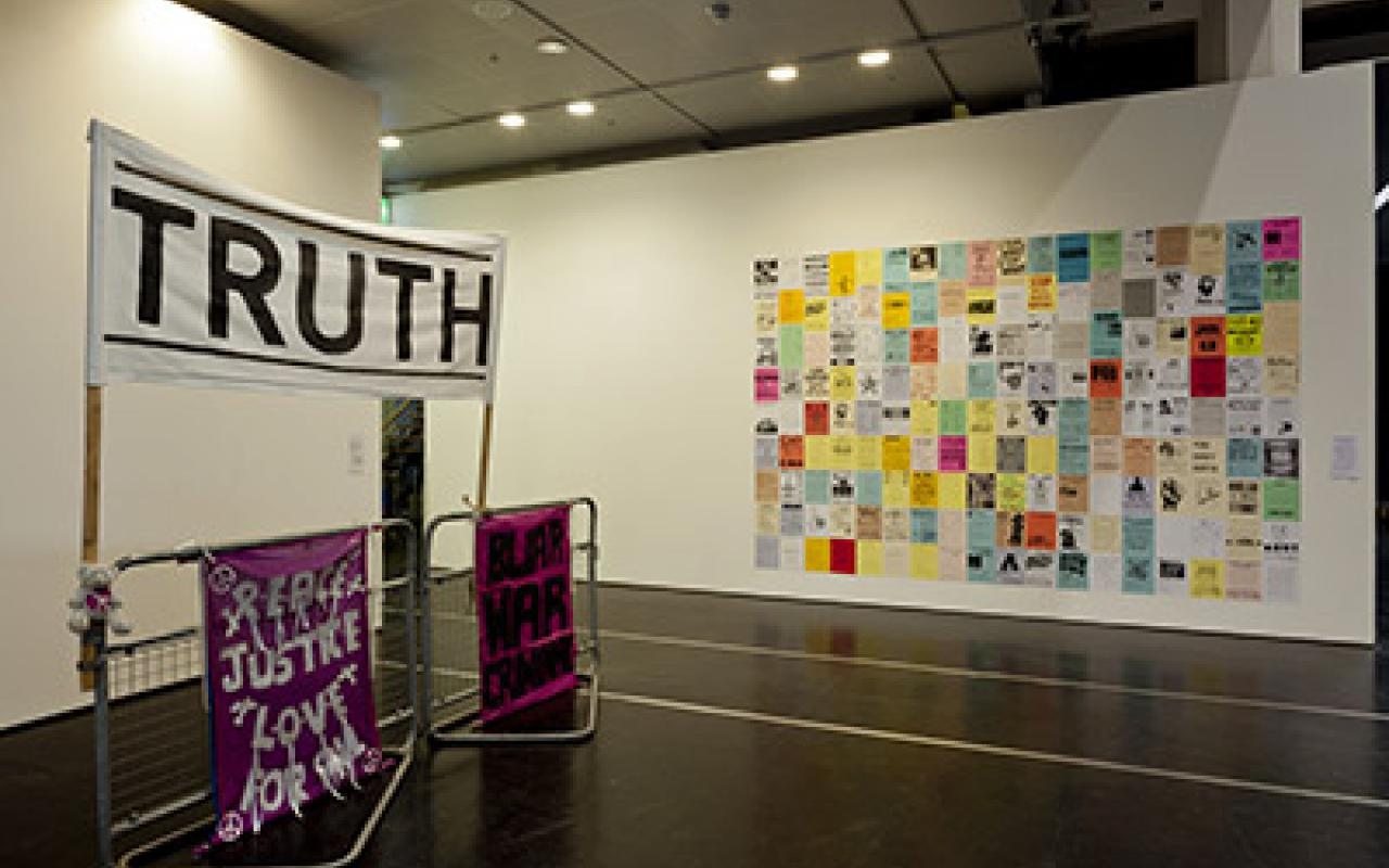 On the left half of three banners are visible. On one is 'Truth'. On the right half of the image sticking on a wall many papers. They are equipped with color and text. They form a large rectangle in their mass.