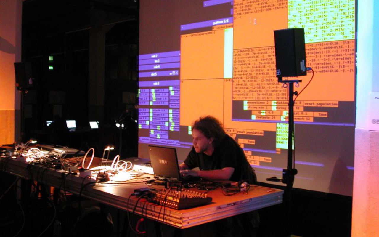 Ein Softwareentwickler bei seiner Arbeit. Der Zuschauer kann auf einer großen Videoleinwand das Programmieren optisch mitverfolgen.
