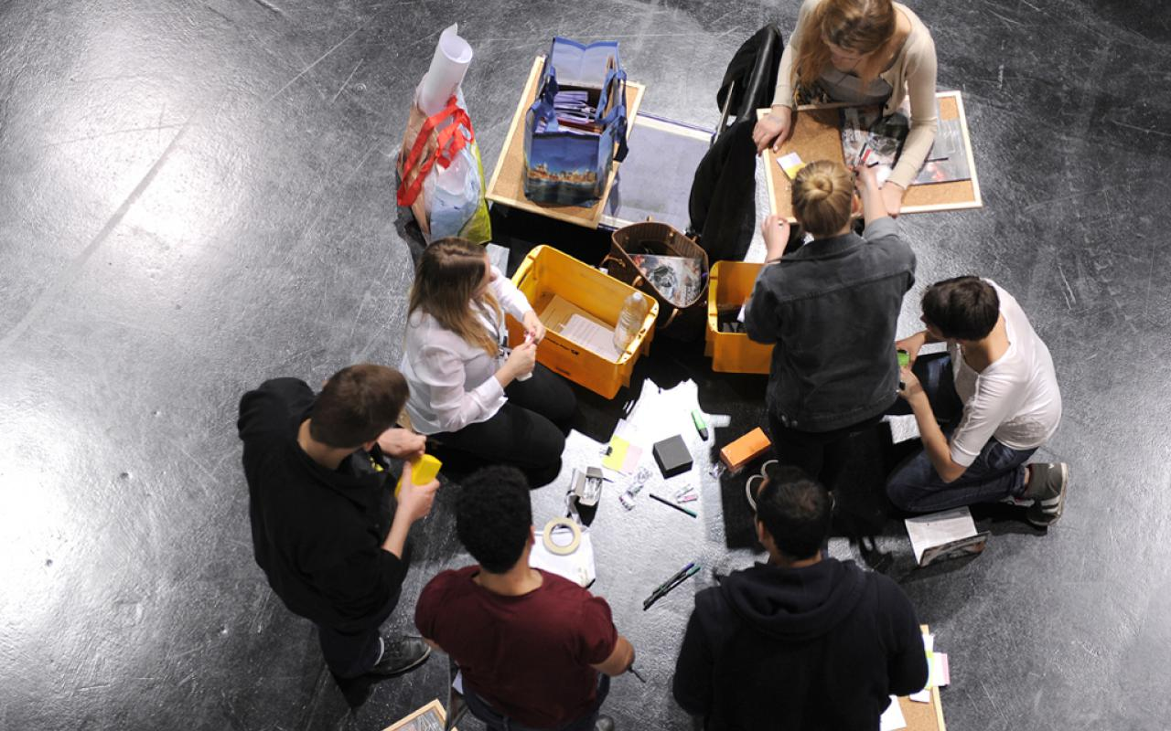 A group of pupils sitting on the floor and tinkering.