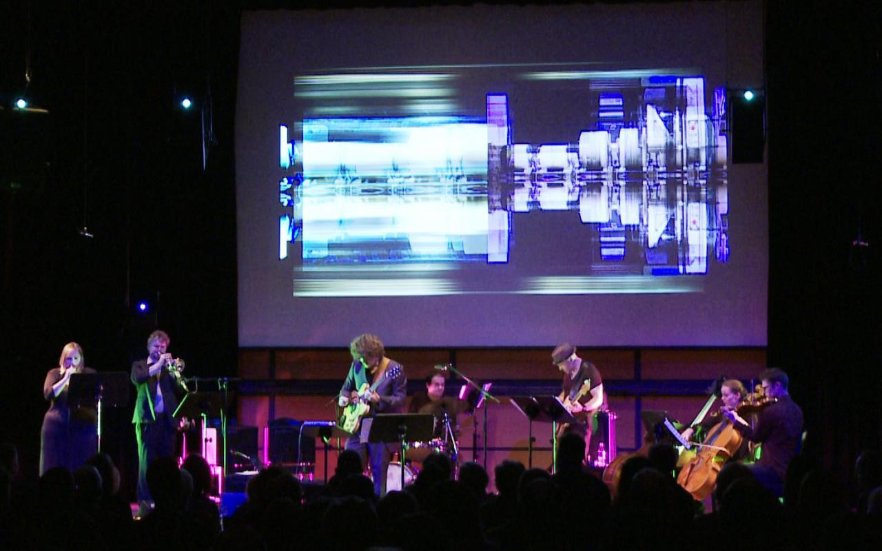 Musical band on a stage. Above them in the background futuristic video animations.