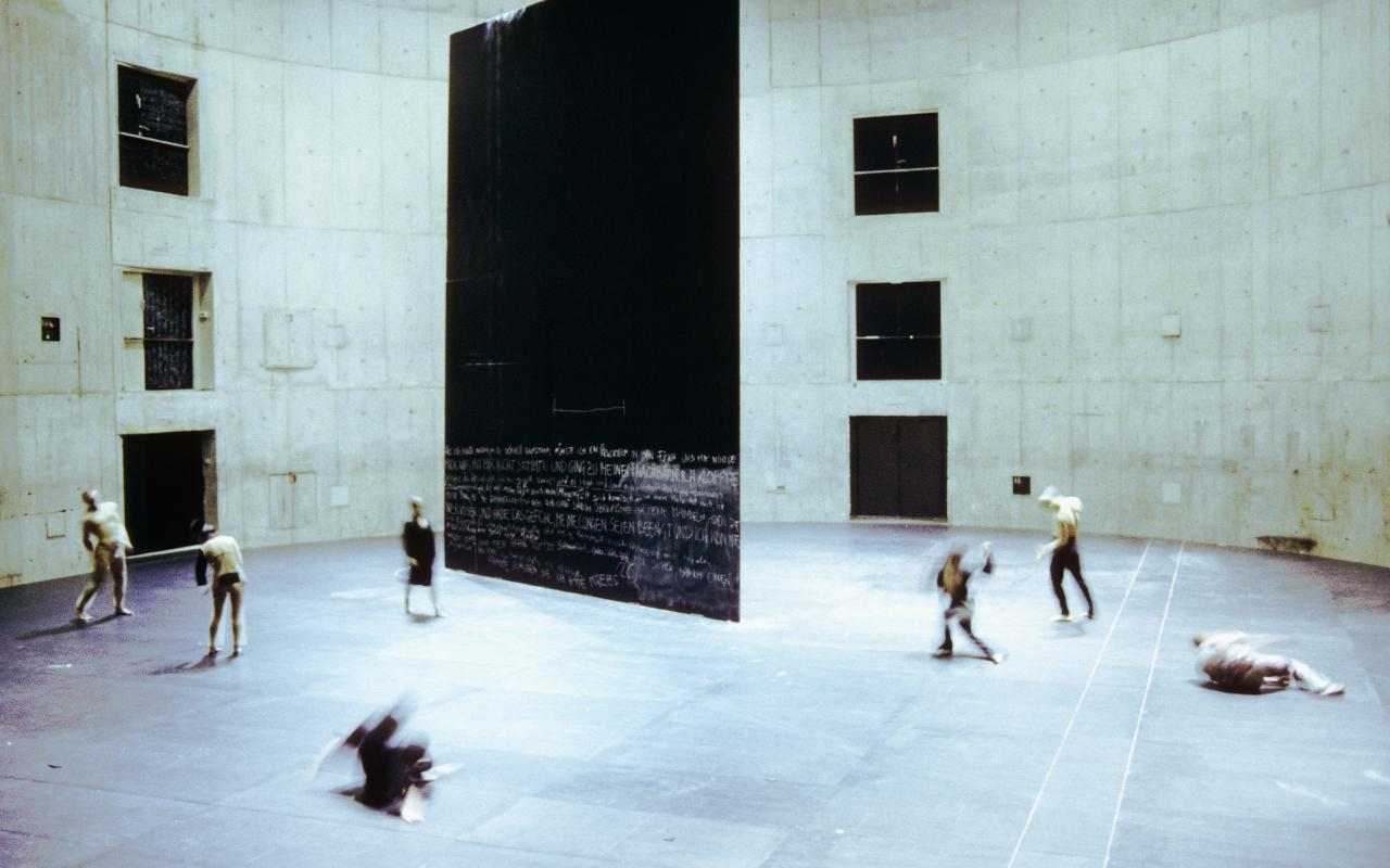 Seven dancers move around a large rectangular black wall that is structured a theatrical space.