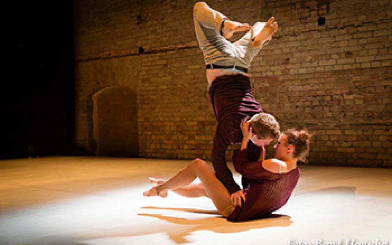 Ein Tanzpaar auf der Bühne. Während dieser auf ihren Hüften einen Handstand macht, versucht sie ihn zu küssen.