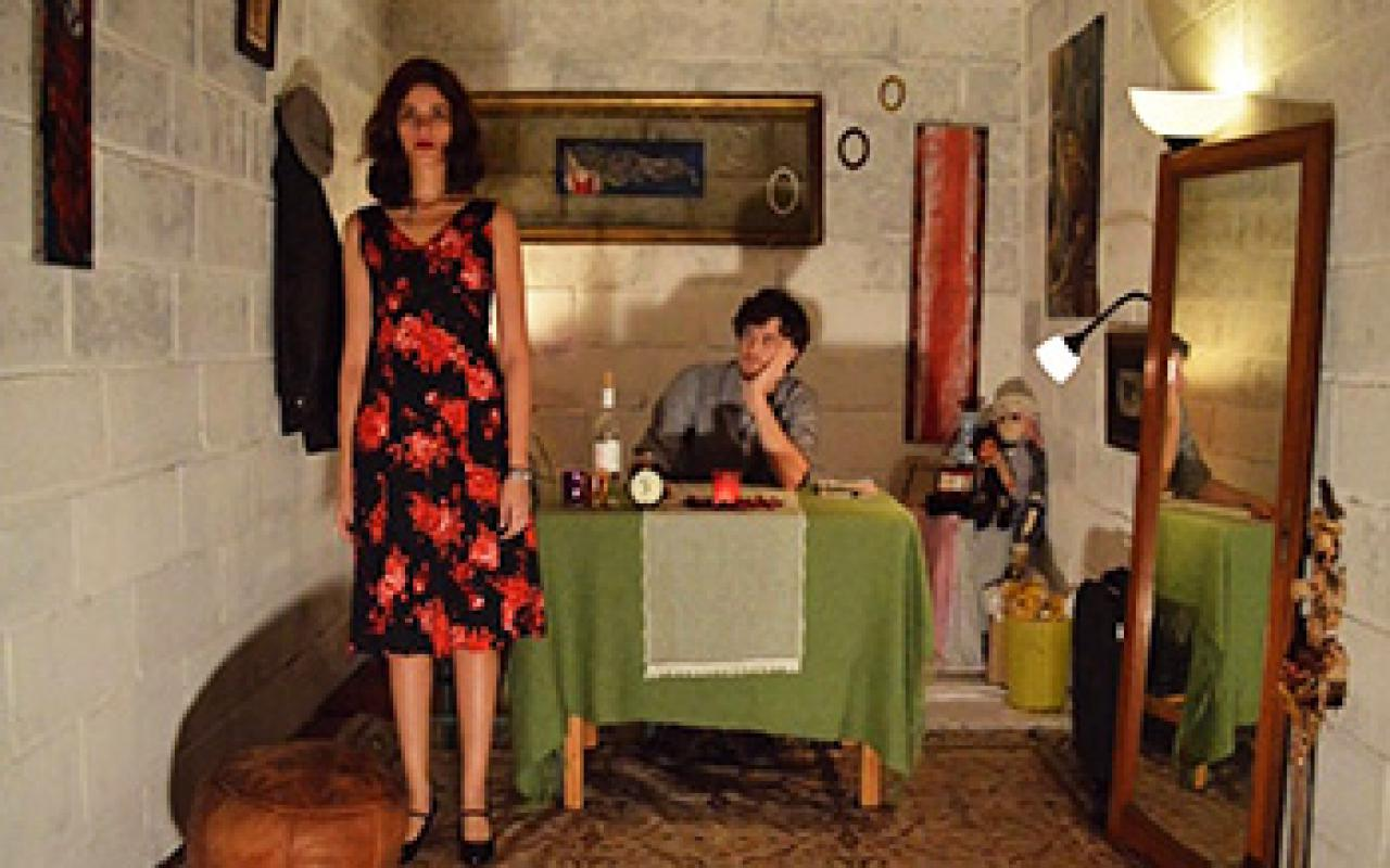 View in room with mirror and table. This has a green tablecloth. On the table sits a man. Next to him stands a woman in a black red floral dress.
