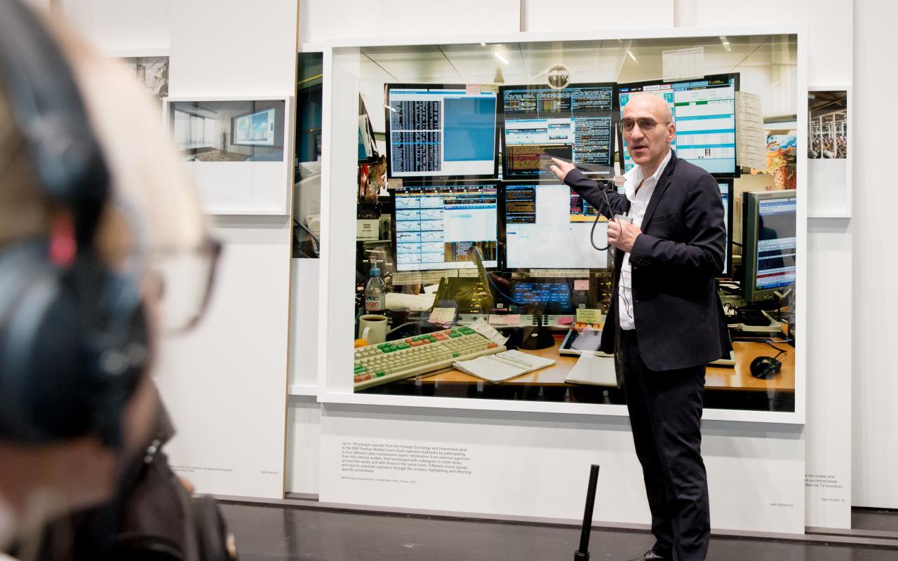 Ein Mann steht vor einem Bild und spricht darüber zum Publikum