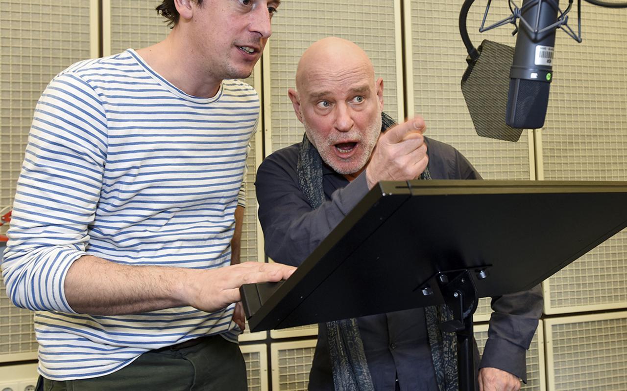 Zwei Männer vor einem Pult und Aufnahmemikrofon