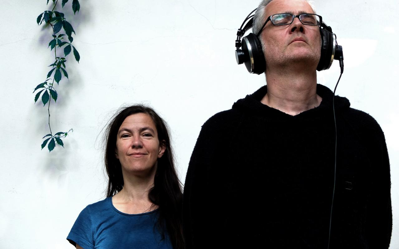Ein Mann mit geschlossenen Augen und Kopfhörern steht rechts vor einer Frau, die in die Kamera schaut