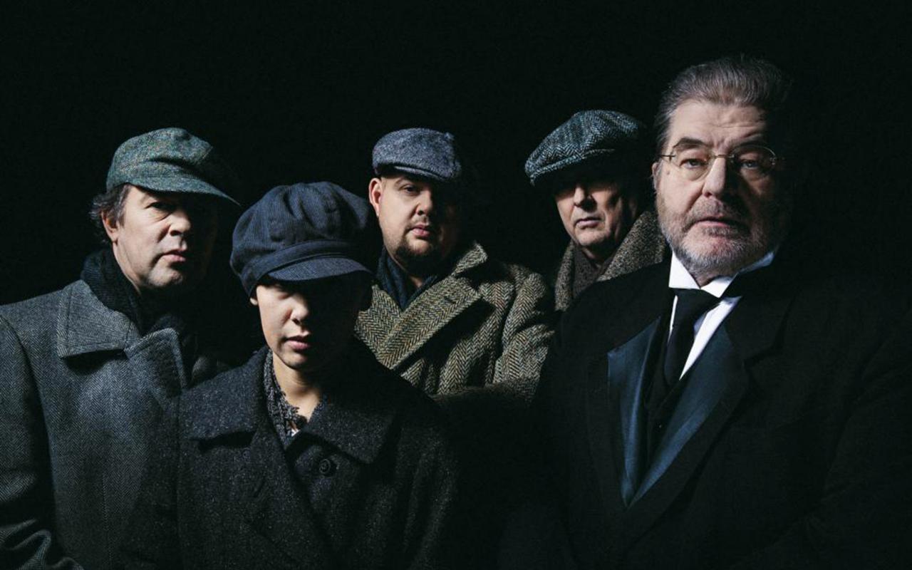 Fünf Personen mit Mantel. Vier davon tragen Baskenmützen