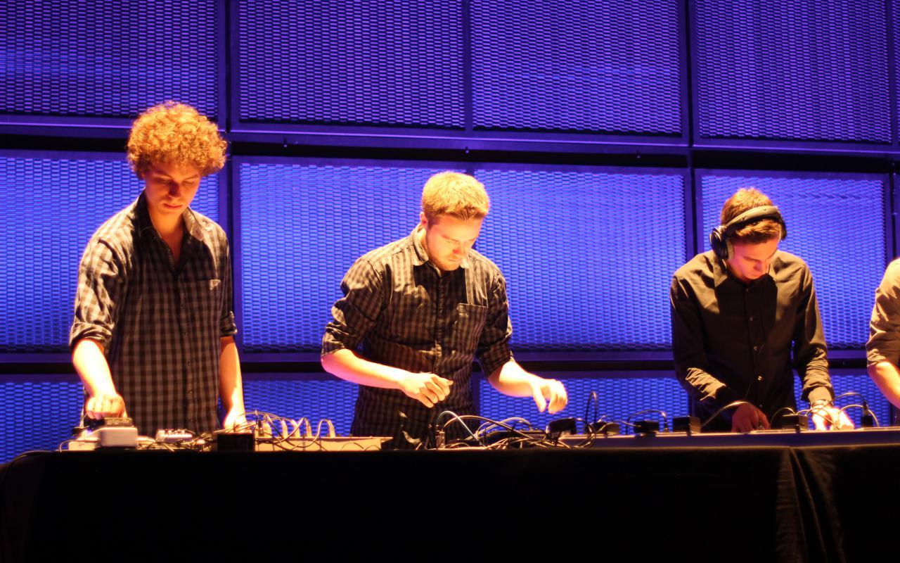 3 Personen auf der Bühne an turntables