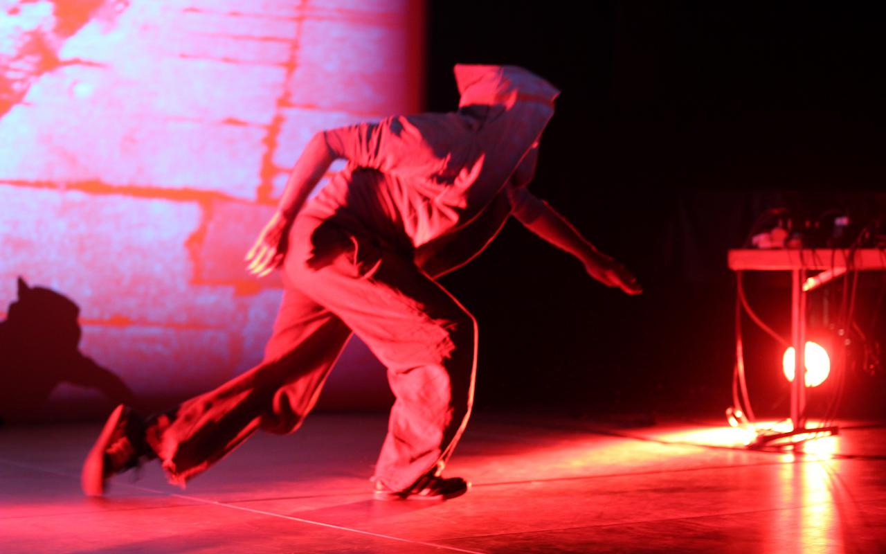 A man on stage with hooded jacket dipped in red light