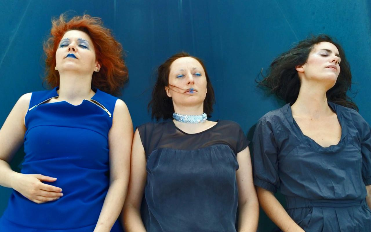 Three women dressed in blue and wearing blue makeup, lying on the blue tarp