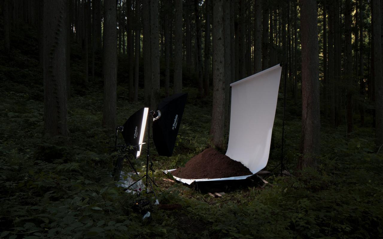 Ein gespanntes Laken, auf dem ein Haufen Erde liegt, der beleuchtet wird.