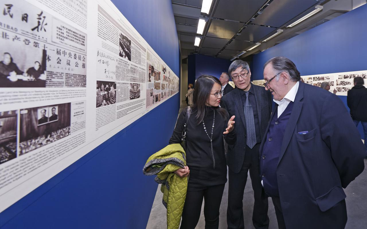 Three people talking in front of some exhibited paintings