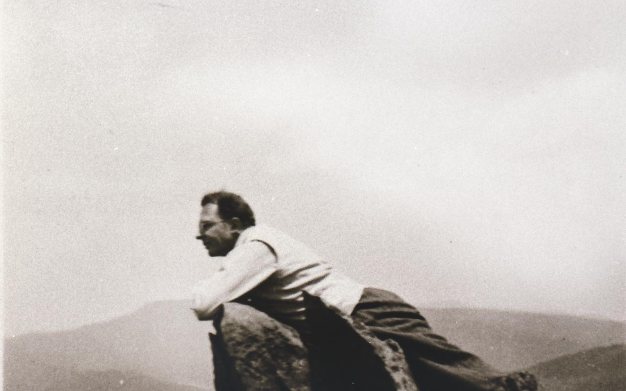 Ein Mann lehnt liegend über eine Bergspitze, im Hintergrund sieht man ein Bergpanorama