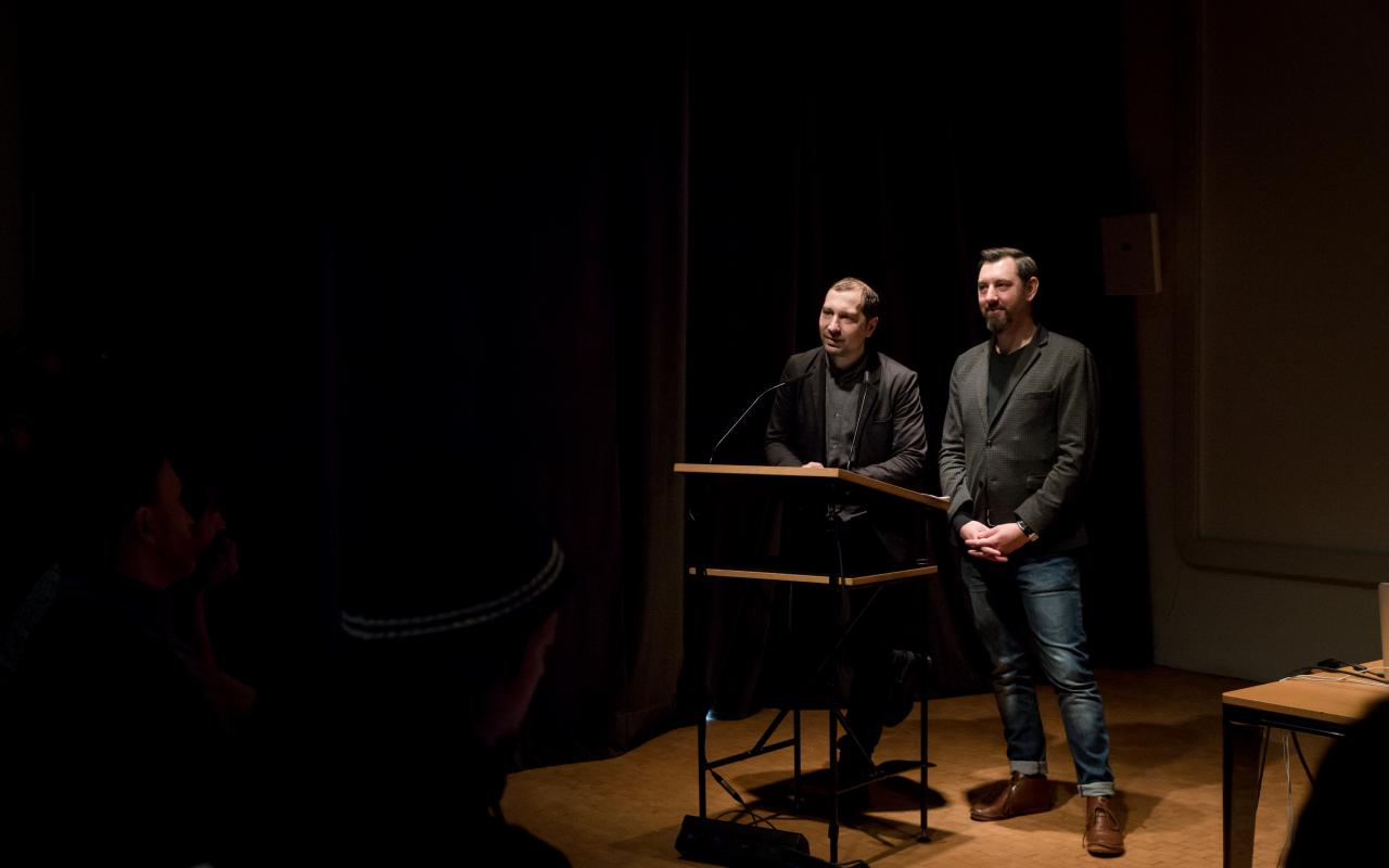Zwo persons stand at a desk and talk to the audience