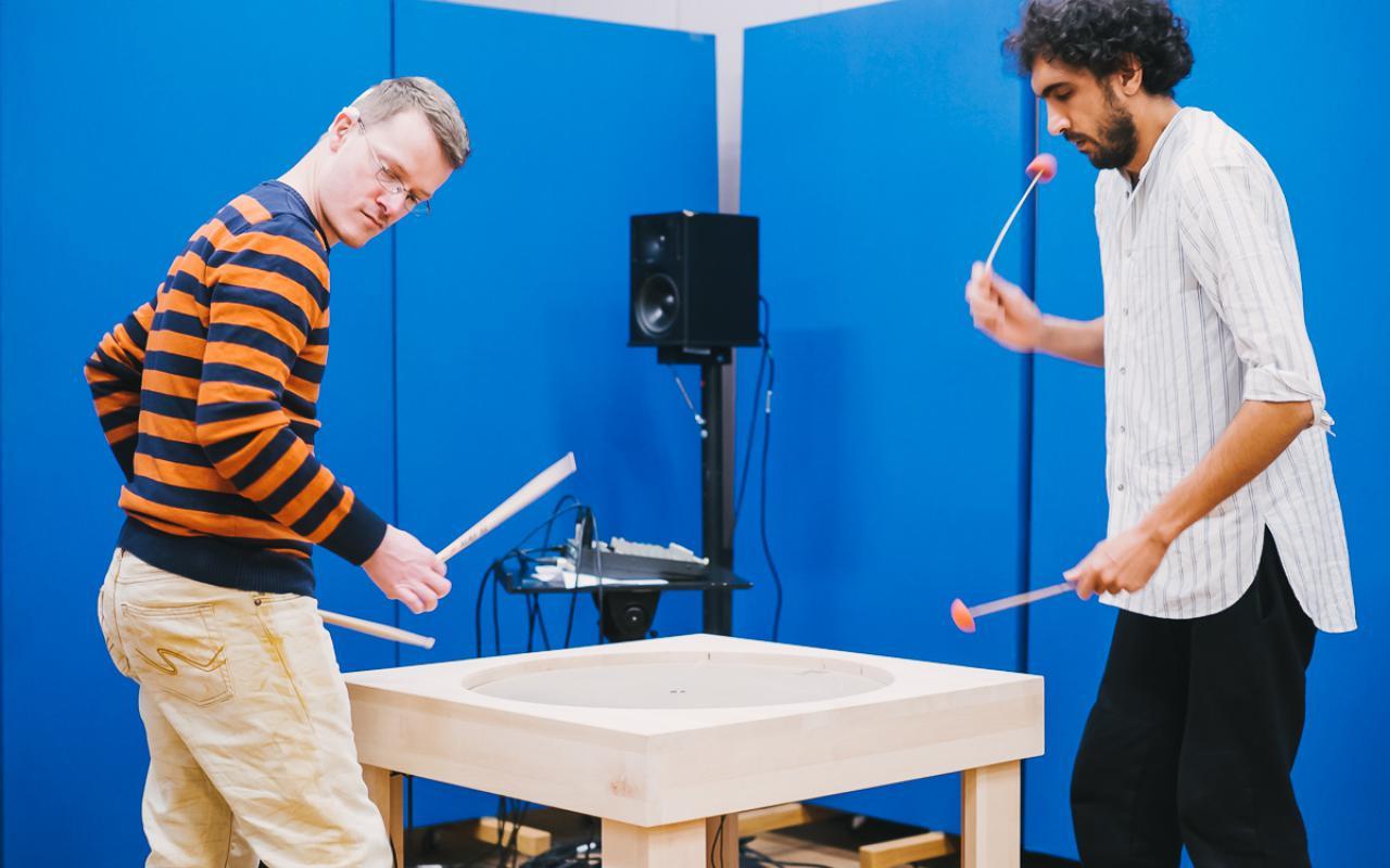 Zwei Männer stehen mit Klöppeln in der Hand an einem Tisch, der eine runde Platte in der Mitte hat.