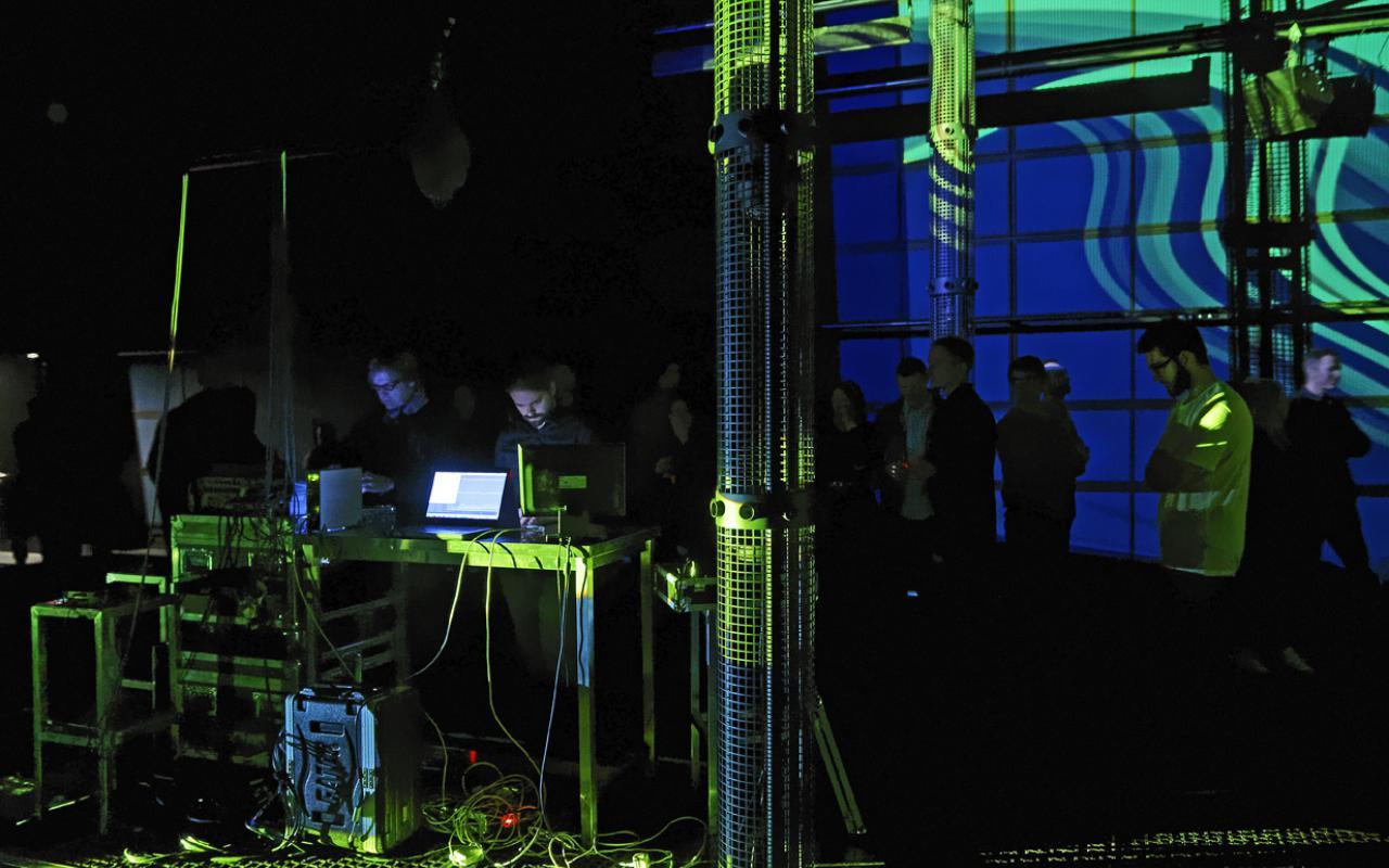 In einem verdunkelten Raum stehen zwei Männer an ihren Laptops