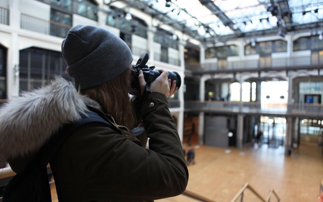 Studierende dokumentieren die Globale. Studentin filmt im ZKM.