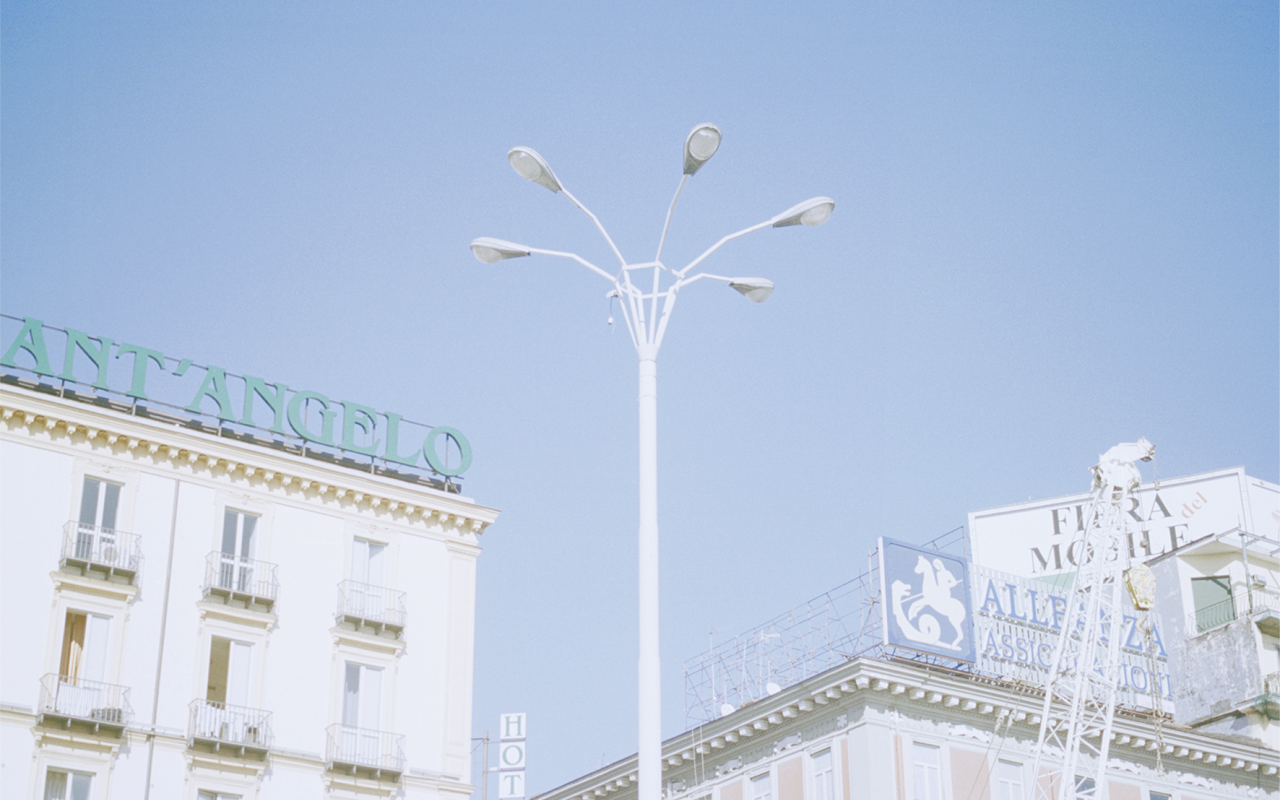 Helle Häuserfassaden und Straßenlaterne vor blauem Himmel.