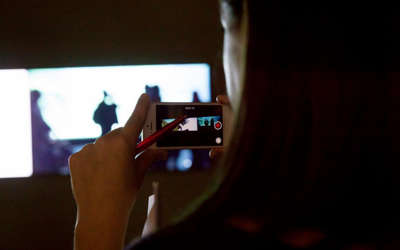 Das Bild zeigt eine Seitenansicht einer Person, die mit ihrem Handy eine Aufnahme eines Kunstwerkes macht.