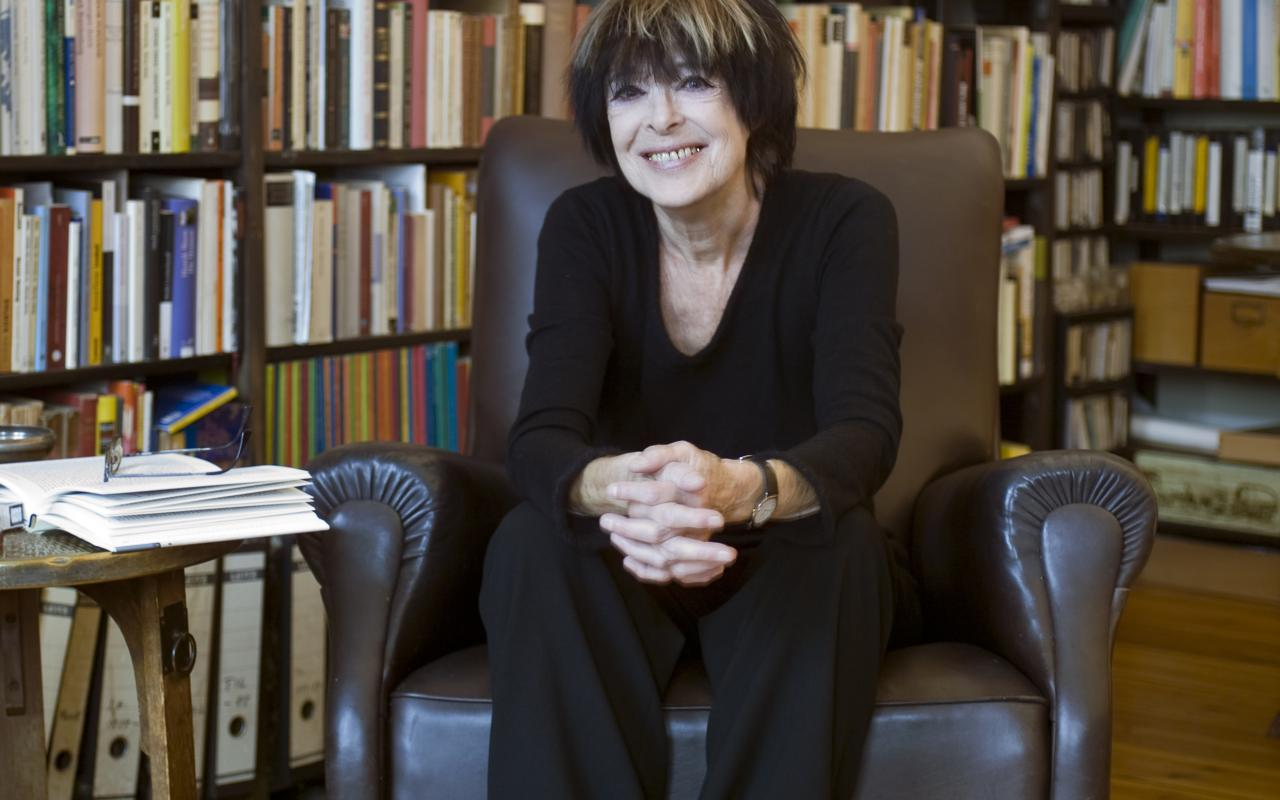 A woman is sitting in a chair in front of a large bookshelf.