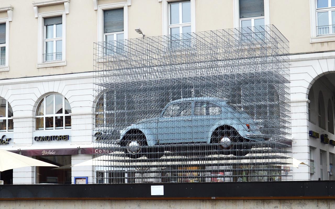 Ein hellblauer VW-Käfer in einem Gittergerüst steht auf einem Podest auf dem Karlsruher Marktplatz.