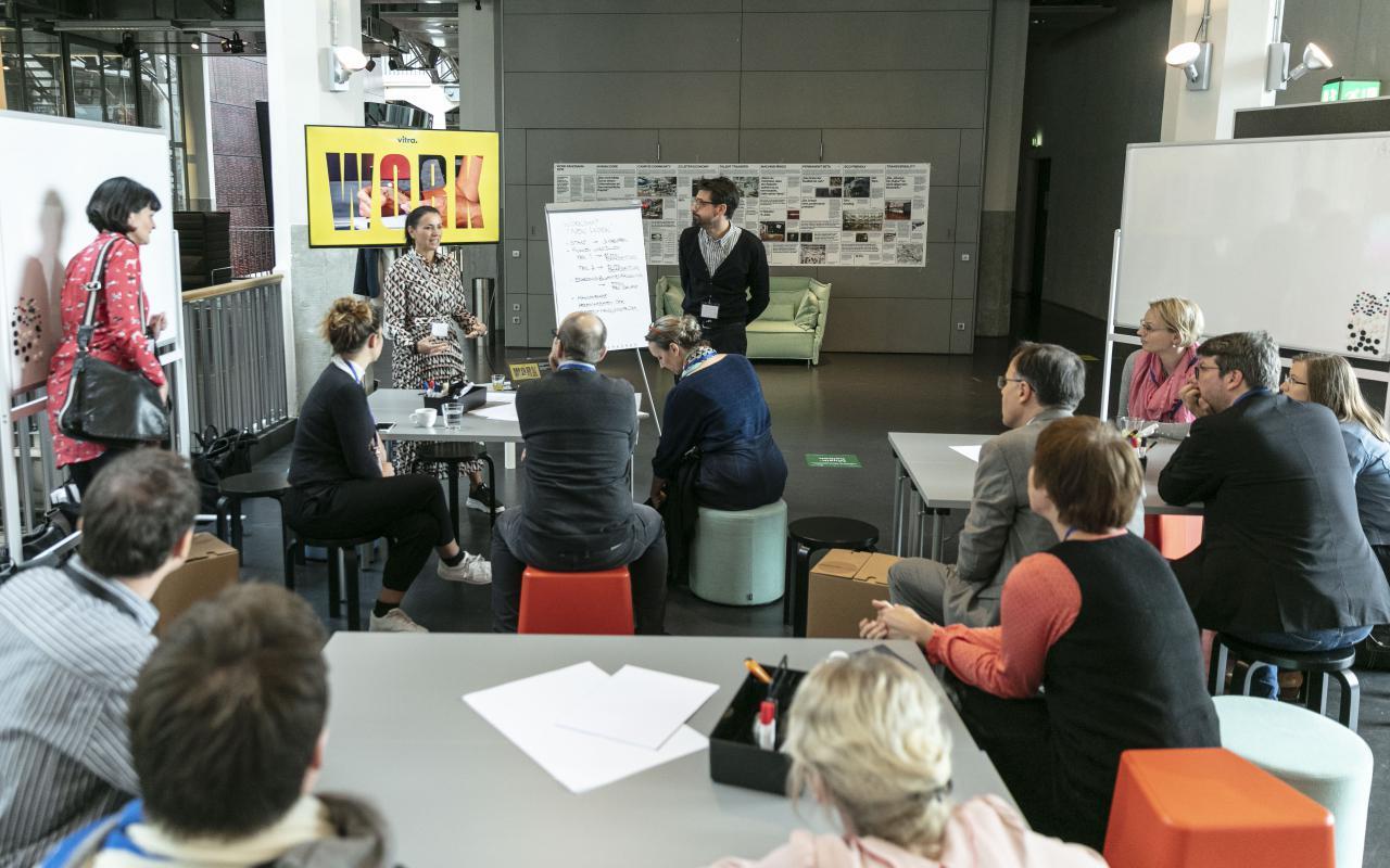 Viele Menschen an Gruppentischen bei einem Workshop