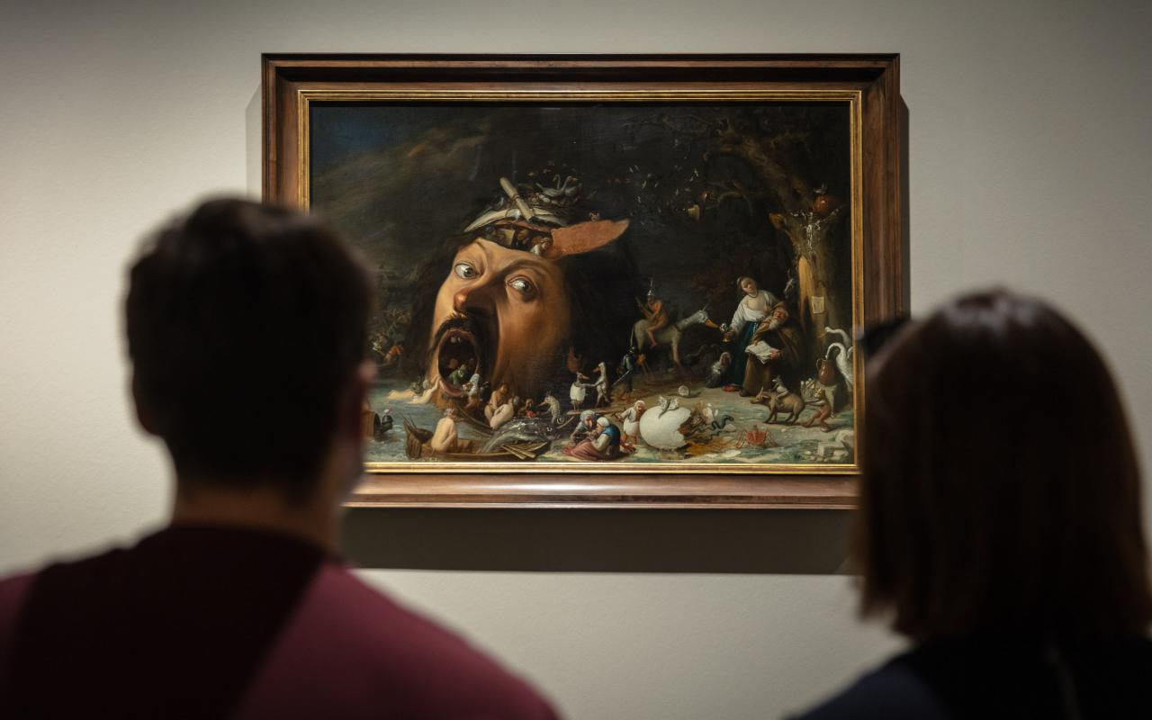 Two people are sitting in front of a picture that shows a huge head with people coming out of its head and mouth. Everything seems very gloomy.