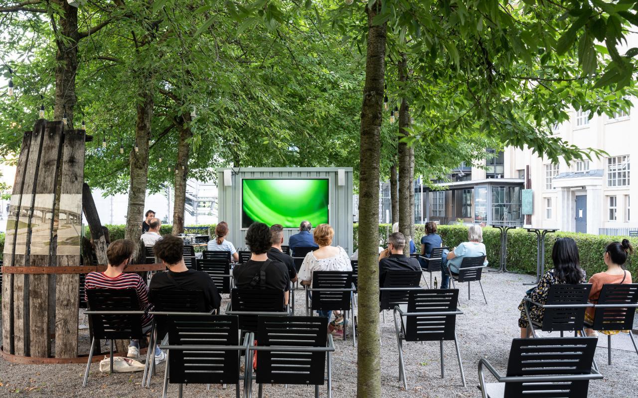 Ein großer Bildschirm mit Menschen auf Stühlen davor im Freien unter grünen Bäumen.