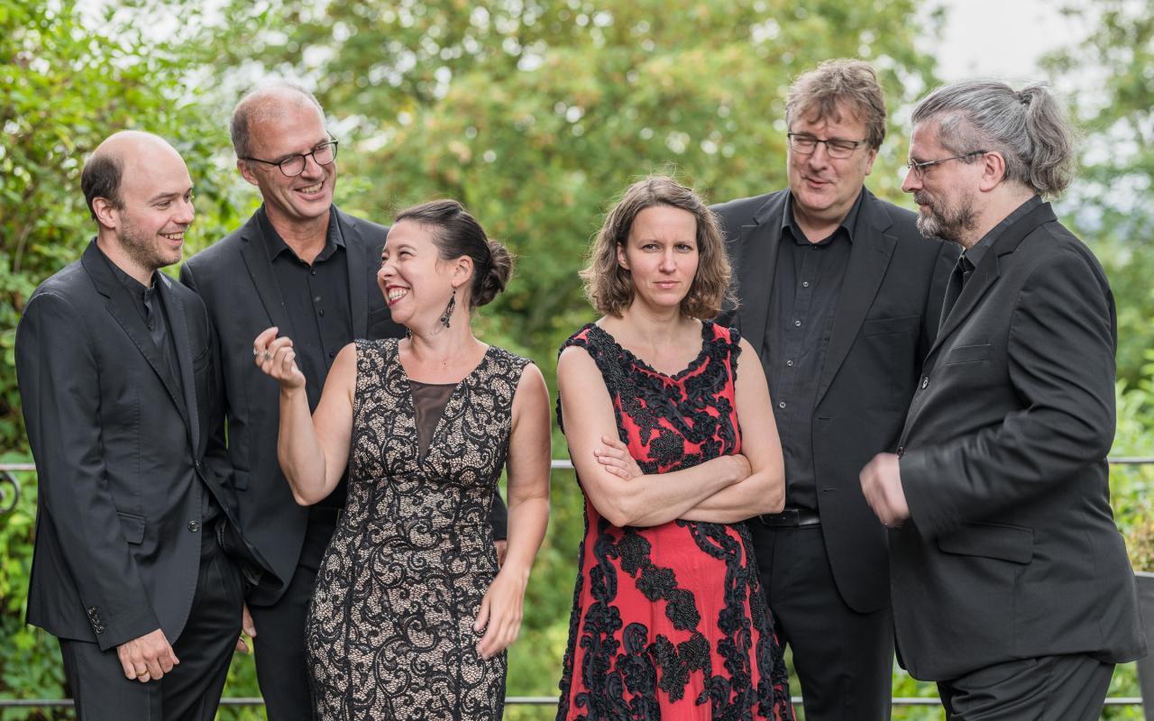 Gruppenportrait von Musiker:innen in schwarzer Abendkleidung.