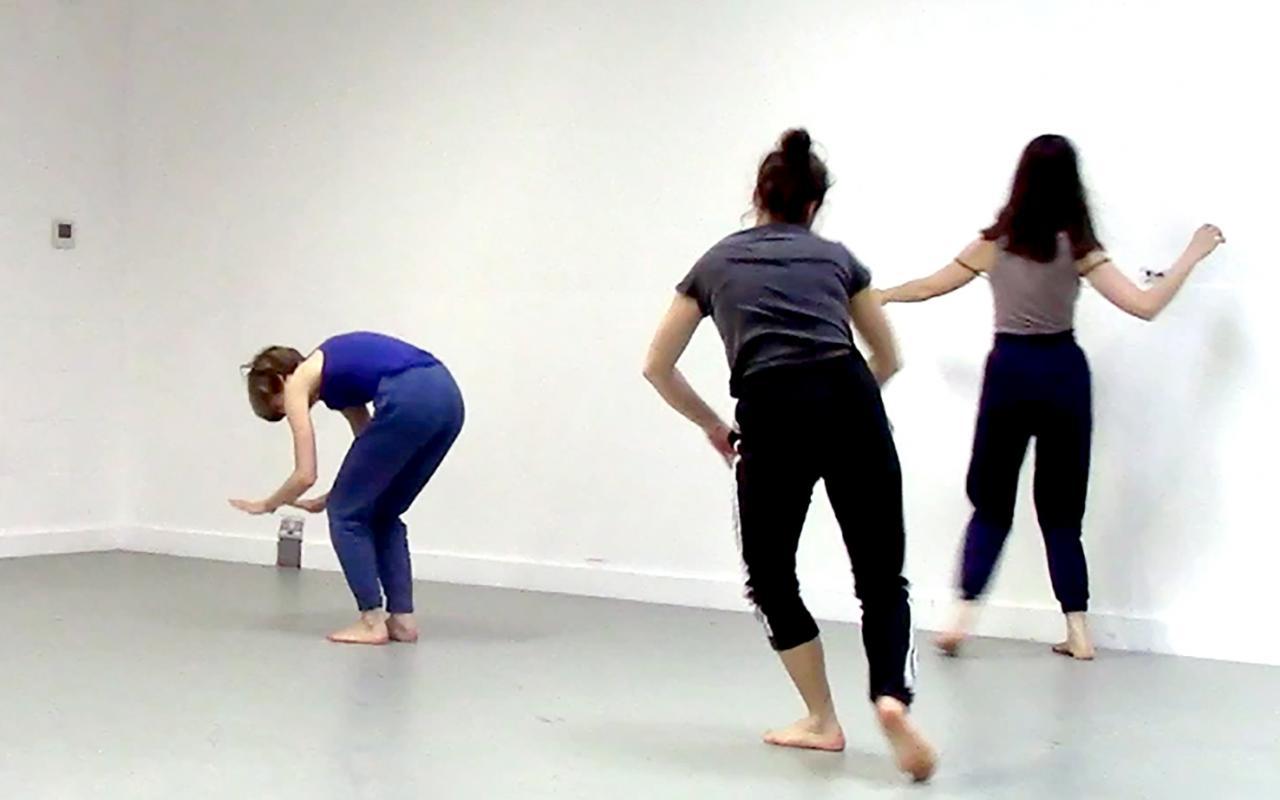Zu sehen sind drei junge Frauen, die in tänzerischer Bewegung sich durch den Raum bewegen.