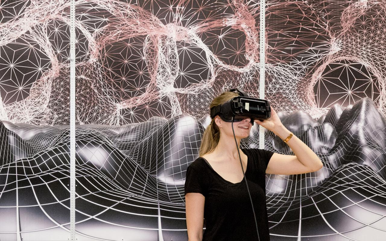 Two women with VR glasses stand in front of a graphic landscape