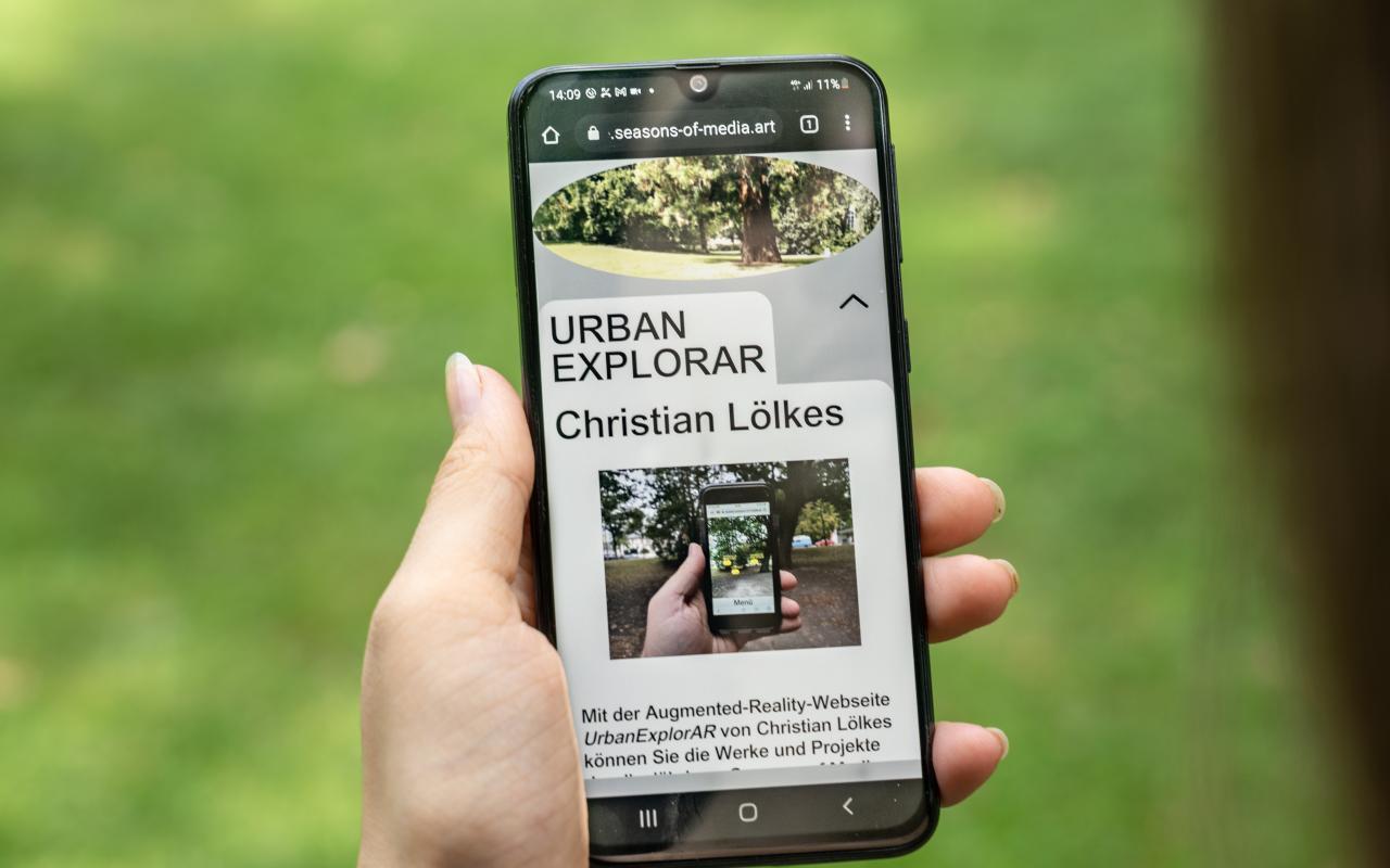 Auf dem Bild ist eine Hand zu sehen, die ein Smartphone hält, auf dem das Werk »UrbanExplorAR« zu sehen ist.