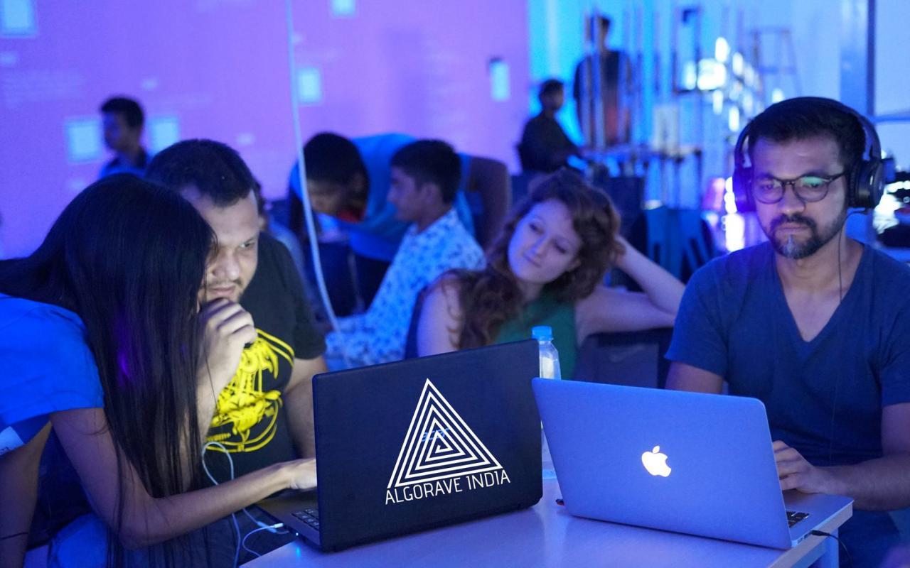 Mehrere Personen sitzen in einem blaülichen Raum an ihren Laptops