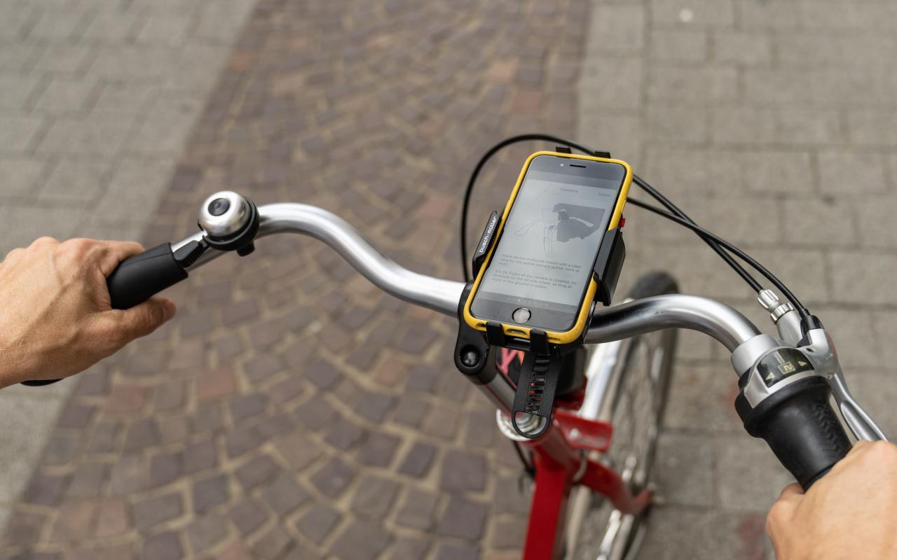 Zu sehen ist ein Ausschnitt von einem Fahrrad mit einem Handy auf der Handy-Halterung am Lenkrad.