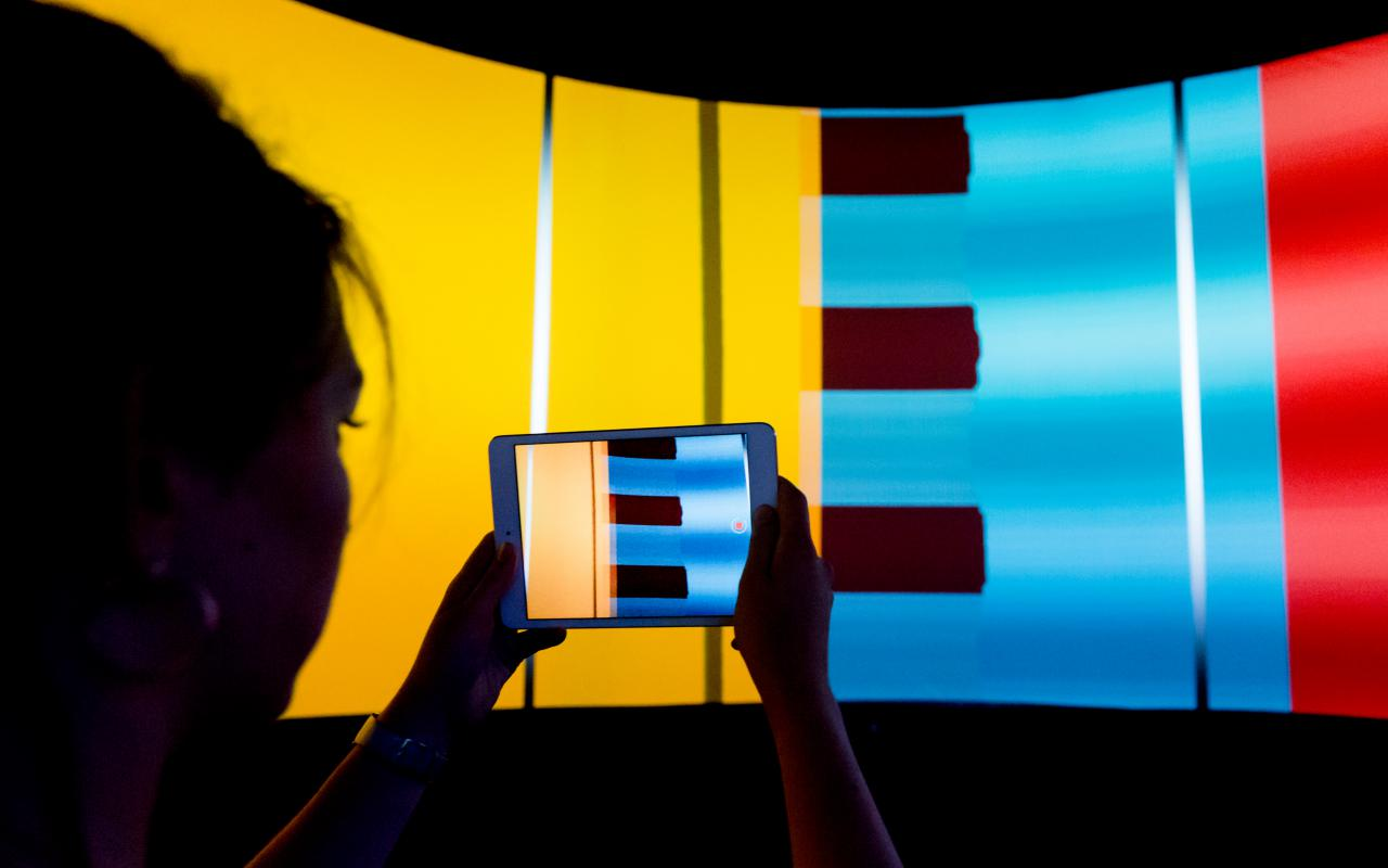 A woman takes a picture of the colorful canvas of the Panolab at the ZKM.